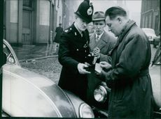 Cop checking documents of car.