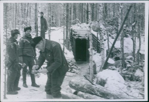Soldier standing, holding a bowl in his hands, other soldiers looking at him.  Finnish Mom on the Karelian Isthmus C.A January 1942