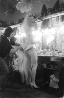 Woman being groomed as mare in make up room.