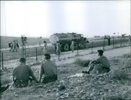 Soldiers siting in the ground while looking the truck in Lebanon.