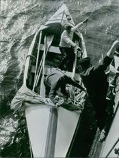 Three men on a boat during a  rescue operation.