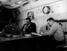 Two US Navy people writing and one eating apple.