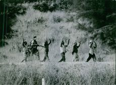 1964 Tanghanyika (Tanganyika)  Peasants with their hands up as a sign of surrender taken prisoner by a soldier.