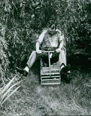 John Ambler riding a grass cutter vehicle.  - 1965