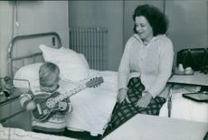 Woman smiling to see the child with leukemia who is playing guitar.