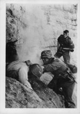 Soldlier trying to pull his fellow comrade from a hole during German and Russian war.  - 1942