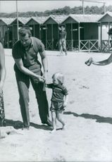 Albert II of Belgium holding his son's hand and walking on sand.