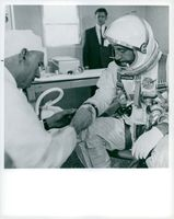 Astronaut Virgil I. Grissom gets his space suits controlled by a NASA technician