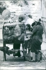 Princess Alexia with other two children talking to women standing beside a shopping cart.