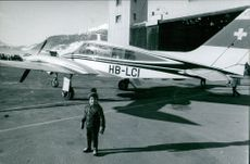 A boy standing beside the plane, 1969.