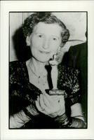 """Nell Reagan receives an Oscar statue in miniature by Robert Board for her role in the movie """"Strange Paradise"""""""
