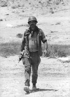 A soldier holding a gun with his shirt open while walking on a desert.