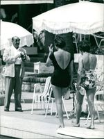 Two women wearing a swimsuit and a man is about to take them a picture.