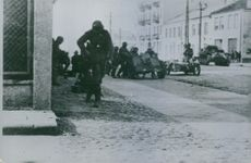 Soldiers waling on the road with their tank.