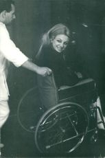 Sandra Milo smiling and being wheeled in wheelchair.