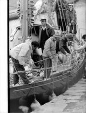 People securing the boat docked on a shipyard.  - Aug 1962