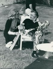 Kirk Douglas sitting on the chair and talking to a woman.
