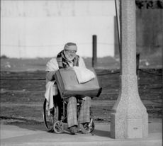 A homeless man without shoes is seated in a wheelchair