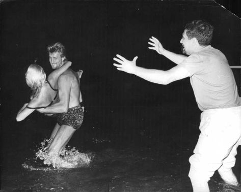 Man lifting a woman and standing in water while another man trying to stop him.