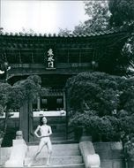 Woman posing in front of Buddhist structure.