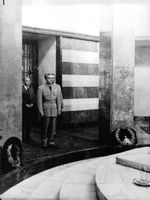A military officer standing inside a room.
