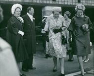 Queen Juliana standing with her husband Prince Bernhard, while their daughters Princess Beatrix (white dress) and Princess Margriet are walking together