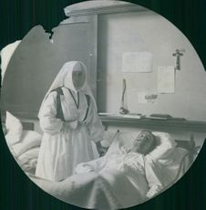 A wounded soldier lying on bed in a medical facility in Holland, whilst a nurse standing beside looking after him. 1914
