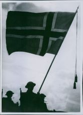 Soldiers marching in street holding flag in hands.