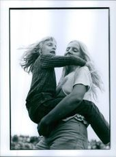 A woman lifted up a girl in her arms and smiling.
