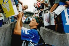 Writing autographs are part of Thomas Enqvist's work during the Australian Open.