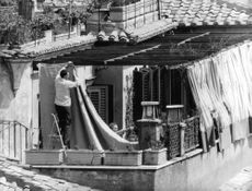 Brigitte Bardot sitting  on terrace of a house.