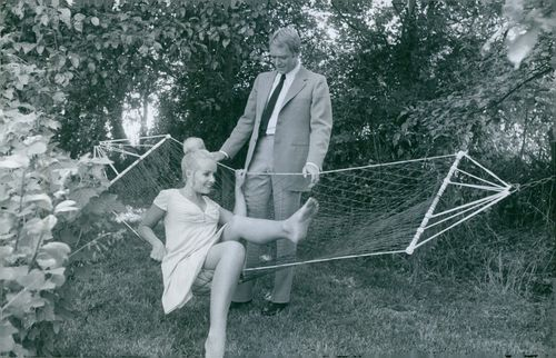 A man looks on as Marie-France Boyer gets on the hammock.
