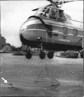 With a helicopter landing net captures a person in distress (arrow) in the water.