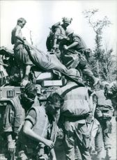 Soldiers collecting useful items of war.