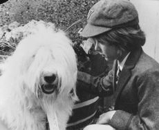 Film scene of a crying boy pampering a dog.  - 1976