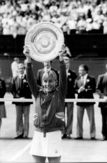 Martina Navratilova proudly holds his trophy after defeating Chris Evert in the Wimbledon Championship
