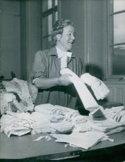 Woman holding white cloth in her hands for donations. 1947