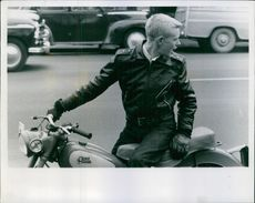 Cunard Yankeens siting on the motorcycle and looking back, wearing a leather jacket.