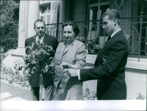 Princess María de las Mercedes of Bourbon and her child Juan Carlos I of Spain are doing something with a plant, while Count of Barcelona Infante Juan is watching the plant