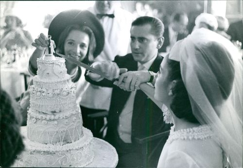 A married couple cutting a cake in a weeding.