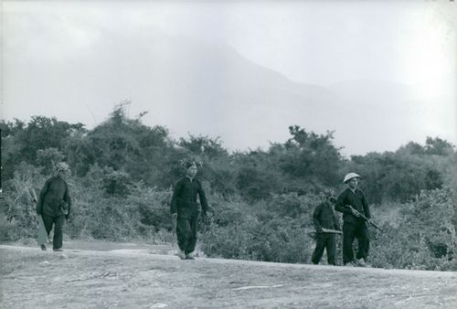 Armed man walking on road in Vietnam, February 1962.