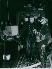 Firemen in the street receiving instructions from men in the blazing building, by means of walkie-talkie, used for the first time in the fire-fighting action.