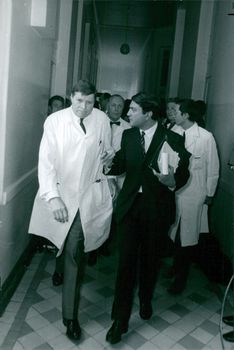 People discussing and walking in corridor.