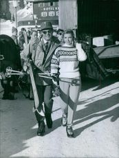 Toni Sailer walking with a woman along with his skiing equipment.