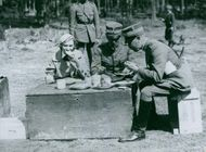 Soldiers sitting having breakfast together in the forest.
