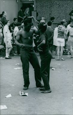 Two hippies dancing in the street.