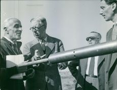 Carl XVI Gustaf of Sweden standing with other people.
