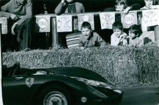 Children watching a car race competition. 1968.