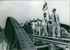 People marching in the supervision of a man holding a flag.