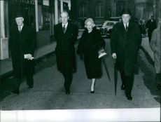 Harold Macmillan and Lady Dorothy Macmillan walking together with a man beside them.